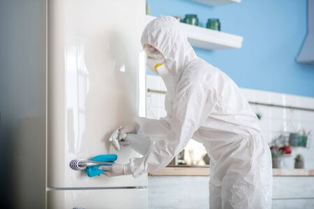 Kitchen disinfection. Woman in white workwear and respirator disinfecting the fridge
