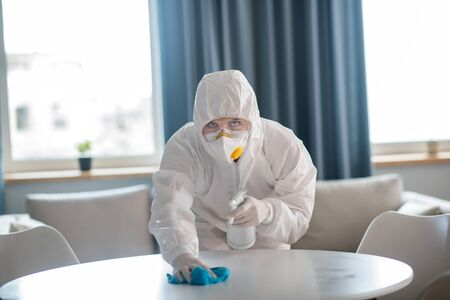 Table surface. Woman in white workwear and protective gloves cleaning the table surface