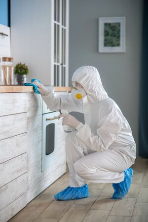 Room disinfecting. Woman in white workwear and protective gloves disinfecting the room