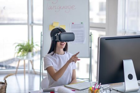 So close. Dark-haired girl sitting at the table wearing vr headset and pointing to something Archivio Fotografico