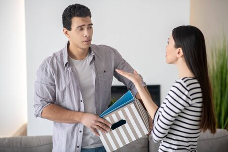 Young upset husband with a box and long-haired wife gesturing with a hand, they are standing arguing.