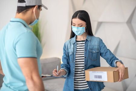Receipt of parcel, signature. Dark-haired young woman with a parcel signing a document held out by a man in a cap, both wearing protective masks.