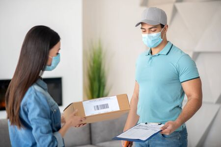 Parcel delivery. Muscular young man with a document, long-haired woman with a parcel, standing opposite each other in protective masks.