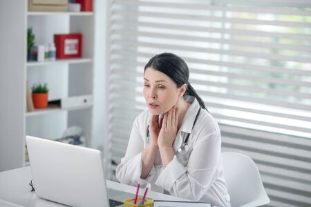 Working process. Successful pretty woman in a white robe sitting in front of a laptop carefully looking at the screen in her office.