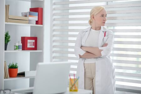 Medicine, worker. Adult woman in a white coat standing near the window, arms folded on her chest, strictly looking to the side. 写真素材