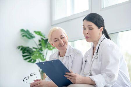 Prescriptions. Two female doctors reading the prescription list 写真素材