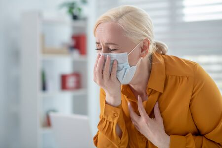 Virus, cough. Fair-haired woman in a yellow blouse in a protective white mask holding on to her face and chest feeling ill