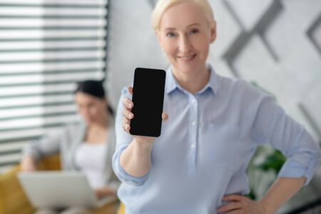 Smartphone screen. Joyful blonde woman in a light blouse holding a smartphone showing screen, a brunette is in the back of the room.