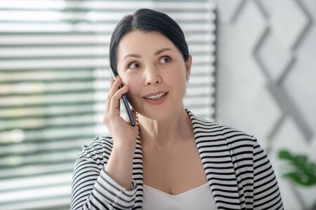 Nice conversation on smartphone. Contented brunette woman talking holding smartphone near ear smiling looking to the side. 写真素材