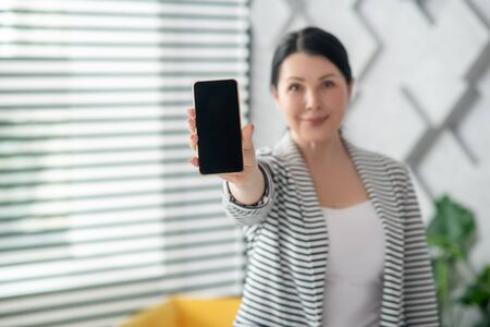 Always in touch. Dark-haired smiling woman standing with outstretched hand showing smartphone screen, positive.