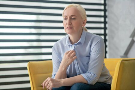 Complaints, health. Sad adult woman with blond hair sitting in a chair near the window talking frowning forehead. Stockfoto