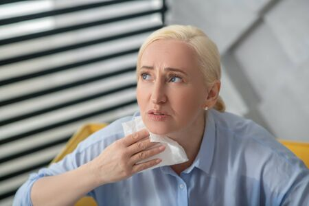 Health, complaints. Unhappy adult woman in a light blouse with a paper napkin near her neck looking sadly up and to the side.