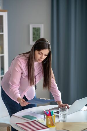 Busy day. Young woman in a pink blouse standing at the table and looking busy Foto de archivo