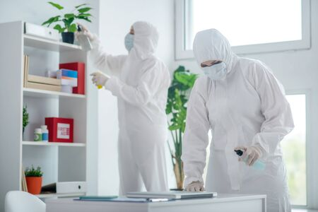 Protective measures. Medical worker in protective clothing and medical mask disinfecting table, another worker standing behind, cleaning closet Reklamní fotografie
