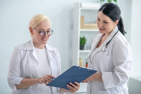 Positive dynamics. Two female doctors reading the medical history and looking positive
