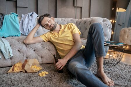 Sad mood. Upset man in jeans and a yellow tshirt with a beer in his hand sitting on the floor near the sofa at home. Standard-Bild