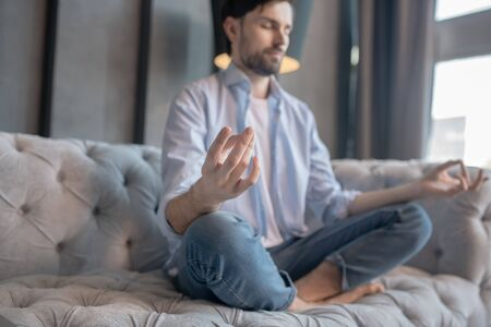 Balance. Young adult man with a calm face with closed eyes, arms to the sides, legs crosswise, on the sofa at home.