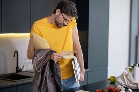 Busy, rush. Serious man in glasses with papers looking at a document talking on a smartphone, standing at home near the table Фото со стока