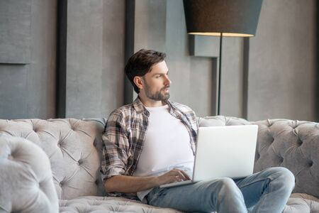 Thoughts. Pensive young adult man in a plaid shirt sitting with a laptop on the sofa, looking to the side, hands above the keyboard Фото со стока