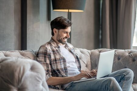 Time for yourself. Young adult man with laptop sitting at home on the sofa, cheerful smiling