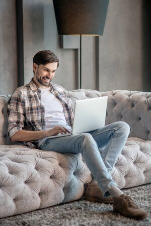 Free time. Dark-haired bearded man sitting leaning back on sofa with laptop looking at screen smiling
