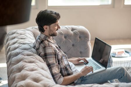Good mood. Dark-haired bearded young man with laptop looking smiling at the screen of his hand above the keyboard, in the room on the couch Фото со стока