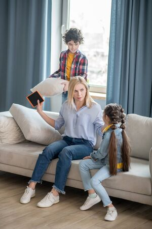 At home. Curly boy and dark-haired girl fighting, boy holding cushion, blonde female trying to calm them down