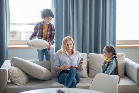 At home. Curly boy and dark-haired girl fighting with cushions, tired blonde female sitting on sofa, checking something on tablet Stockfoto