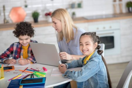 At home. Curly boy and dark-haired girl sitting at table, blonde female sitting between them with laptop, girl smiling into the camera