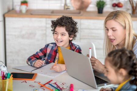 At home. Curly boy and dark-haired girl sitting at table, doing their assignments, discussing something, smiling, blonde female helping them, checking something on laptop