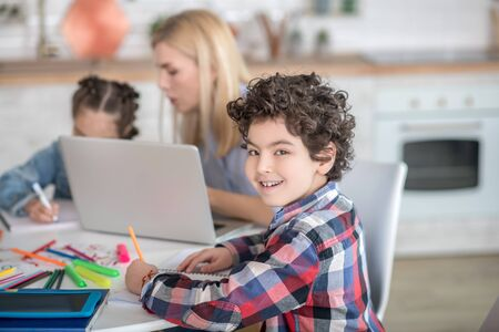 At home. Curly boy and dark-haired girl sitting at table, doing their assignments, blonde female helping them, explaining something to girl Stockfoto