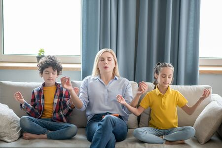 At home. Curly boy, dark-haired girl and blonde female sitting on sofa, meditating Stockfoto