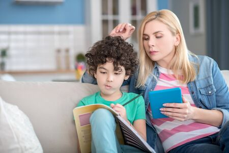 At home. Blonde female holding tablet, checking what curly boy writing in his notebook