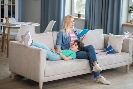 At home. Blonde female holding tablet and reading, curly boy lying on her lap, listening to her