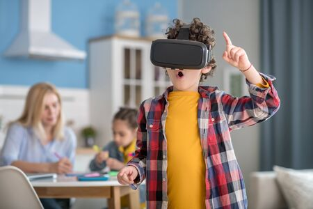 At home. Curly boy wearing vr glasses, looking excited, dark-haired girl and blonde woman sitting at round table, busy with tasks
