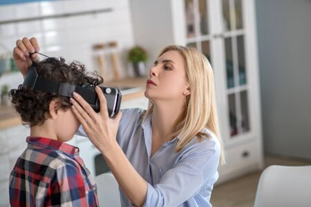 At home. Blonde female putting on vr glasses on curly boy Stockfoto
