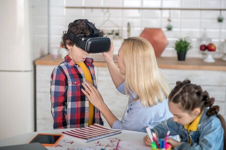 At home. Blonde female putting on vr glasses on curly boy, dark-haired girl sitting at round table, writing Stockfoto - 147518068