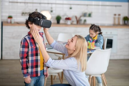 At home. Blonde female putting on vr glasses on curly boy, dark-haired girl sitting at round table behind them, writing