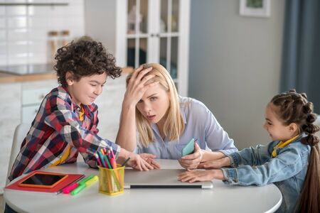 At home. Tired blonde female sitting at table, holding her head, curly boy and dark-haired girl fighting over laptop