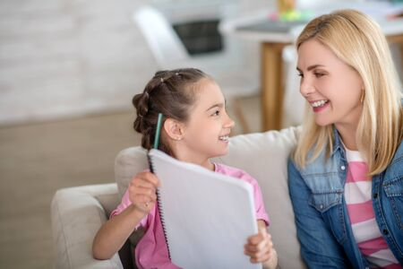 At home. Dark-haired girl and blonde female sitting on sofa, girl showing her notebook to woman, both smiling Stockfoto