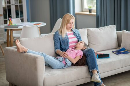 At home. Blonde female siting on sofa with legs crossed, dark-haired girl lying on her lap