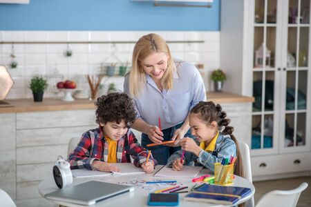At home. Curly boy and dark-haired girl sitting at table, doing their assignments, blonde female standing above them, helping