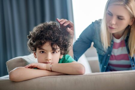 At home. Sad curly boy sitting on sofa, blonde female stroking his hair, trying to cheer him up Stockfoto - 147517715