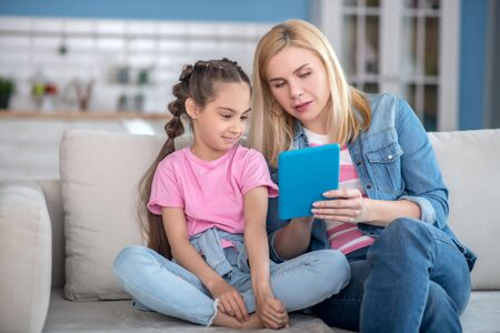 At home. Blonde female and dark-haired girl sitting on sofa, watching something on tablet