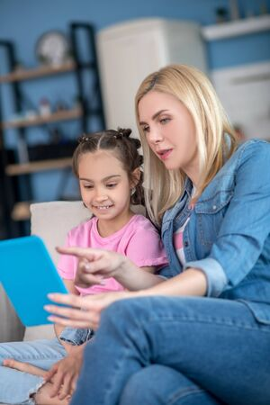 At home. Blonde female and dark-haired girl sitting on sofa, watching something on tablet, smiling Stockfoto