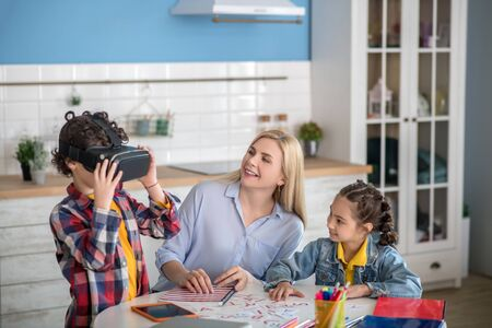 At home. Curly boy and dark-haired girl sitting at round table with blonde female, boy wearing vr glasses