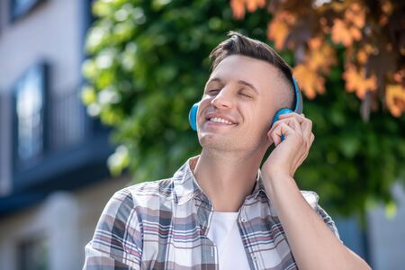 Free time. Smiling dark-haired male wearing headphones, listening to music