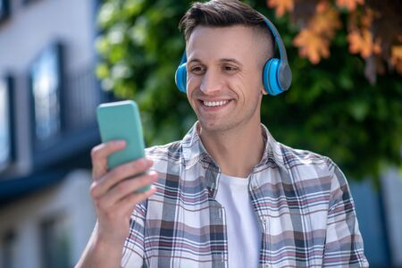 Free time. Cheerful dark-haired male wearing headphones, looking at his smartphone