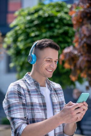 Free time. Smiling dark-haired male wearing headphones, chatting on the phone Фото со стока
