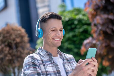 Free time. Cheerful dark-haired male wearing headphones, chatting on the phone Фото со стока